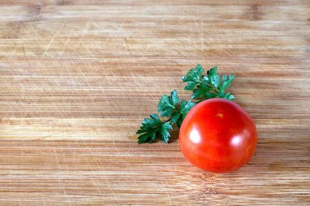 Tomato and wet parsley leaf on a wooden surface, focus throughout the frame. Ingredients for Salad on a Cutting Board
