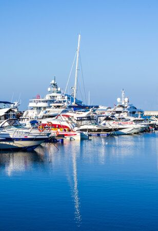 Sochi, Russia - July 20, 2019: yachts parked in the early morning are reflected in the water. Yacht Marina. Vertical frame