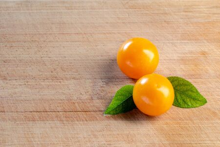 Two cherry plums with green leaves on a wooden surface. Wood texture. Empty space. Close-up