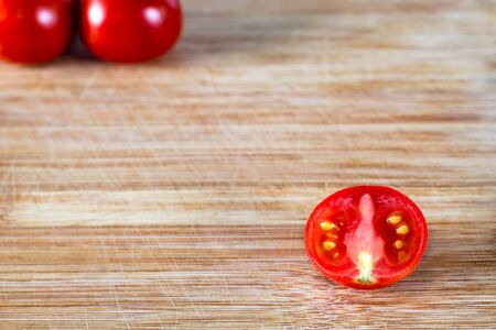 Half cut tomato and two tomatoes on top in the corner, on a wooden surface in the corner, on a wooden surface