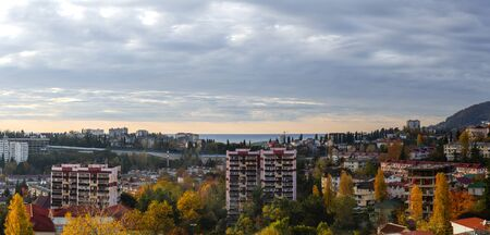 Panorama of apartment buildings in the middle of autumn yellow trees against the backdrop of a sea surface stretching beyond the horizon. Morning cloudy sky. Roofs of houses Фото со стока - 132071704