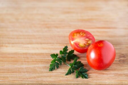Tomato and half a tomato with a sprig of parsley on a wooden surface. Top view at an angle