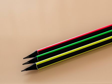 Lead pencils in colorful frames. Cropped objects on a light glass surface. Copy space