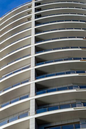 Part of the facade of a high-rise building with semicircular balconies. Vertical frame Фото со стока - 132071605