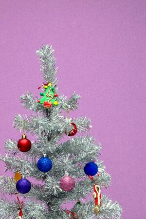 Silver Christmas tree with red and blue balls on a purple uniform background. Cropped vertical frame