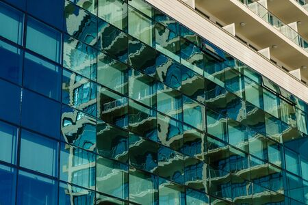 Part of the facade of the building with green glazing and reflection of the structure of the building