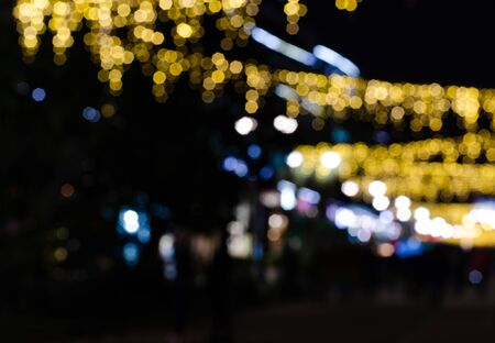 Bokeh from city illumination: yellow lights of air garlands, white illumination of buildings Фото со стока