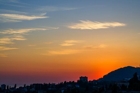 Yellow sunset with clouds over the city by the sea. The sun shines from behind the mountains. Urban landscape at dusk