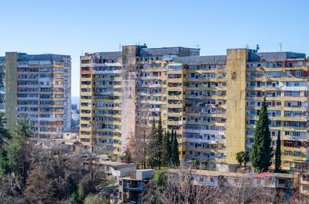 Old panel high-rise apartment buildings lit by the morning sun. The dilapidated buildings in the city. Overhaul example