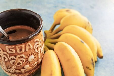 Ceramic Goa coffee mug and bunch of yellow bananas on a blue table