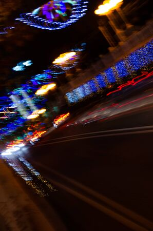 Night city highway with festive illumination. Vertical frame. Blurry shot