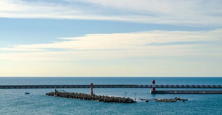 Port infrastructure: ship mooring, red lighthouse at sea and breakwater