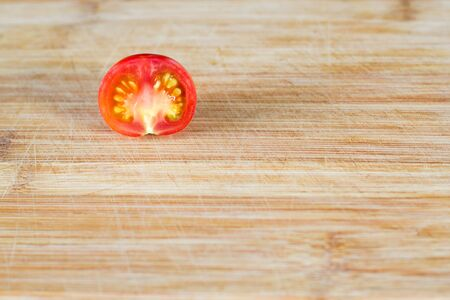 Half a tomato on a wooden surface at the top of the frame. Top view at an angle Фото со стока - 132071585