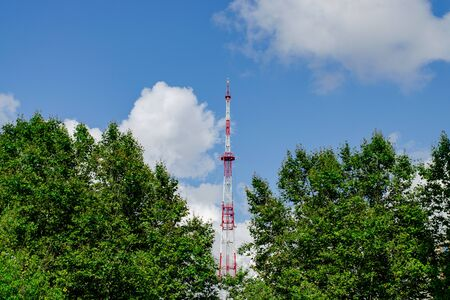 TV tower. Repeater. Green trees. Blue sky with white clouds. Industrial facilities in the city
