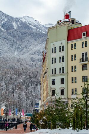 Sochi, Russia - December 29, 2018: Rosa Khutor. The hotel building against the backdrop of a snowy mountain peak. Vertical frame Редакционное