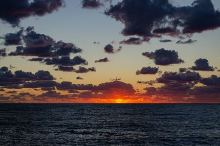 The red setting sun over the sea touches the edge of the horizon. Dark dramatic clouds