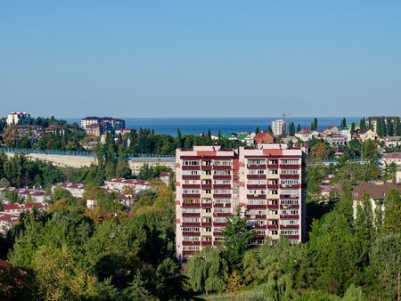 Cityscape with apartment building, red roofs and the sea Фото со стока
