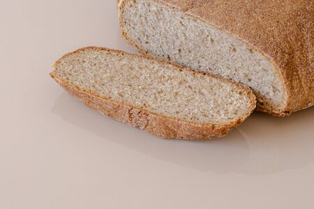Whole grain round bread. Beige glass surface. Chopped chunk