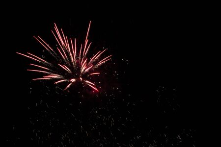 A bunch of red fireworks with yellow sparks in the lower half of the frame