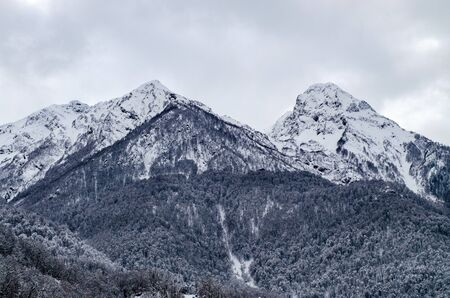Two mountain peaks in the snow under gloomy lead clouds. Harsh winter landscape