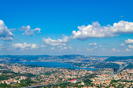 The Baltalimanı quarter and the Fatih Sultan Mehmed Bridge over the Bosphorus under a bright blue sky with white lush clouds. Roofs of Istanbul from a height Редакционное