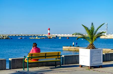 Sochi. Russia - November 6, 2018: a woman in a red jacket is talking on the phone, sitting on a bench at the sea pier with a lighthouse. Decorative palm tree against the background of the sea and fishermen
