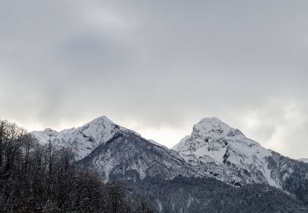 Two mountain peaks in the snow under gloomy lead clouds. Steep cliffs