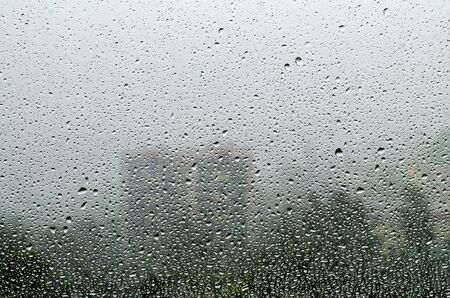 Raindrops on a window pane overlooking the city and trees. Autumn mood Фото со стока