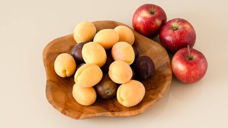 Farm organic plums, yellow apricots and apples. Handmade teak wooden fruit bowl