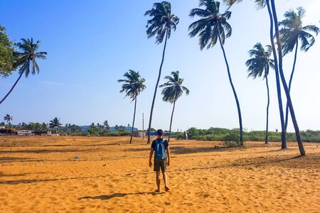 A young man in shorts and with a backpack is walking on the sand under tall palm trees. Tourist under the scorching sun