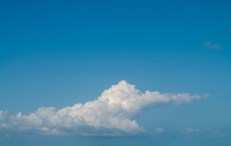 Fluffy cumulus cloud in the turquoise sky. Free space