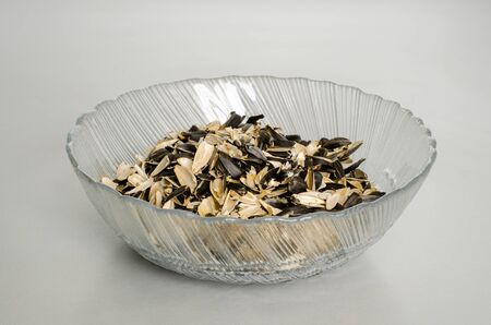 A transparent plate with husks from sunflower seeds. Top view at an angle. After a snack Фото со стока