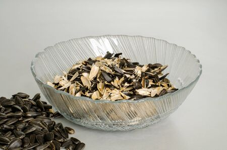 A transparent plate with husks from sunflower seeds. And a scattering of seeds. Top view at an angle
