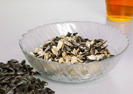 A transparent plate with husks from sunflower seeds. And a scattering of seeds and a cup of tea. Top view at an angle Фото со стока