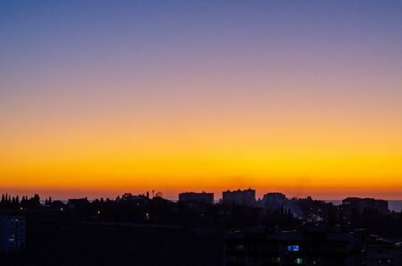 Sunset over the city with silhouettes of houses. Sky to Purple Gradient Orange Фото со стока - 132124629