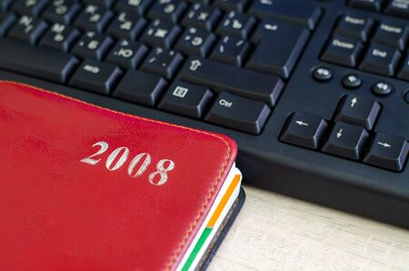 Red notebook and part of the black keyboard. Back to 2008 Фото со стока