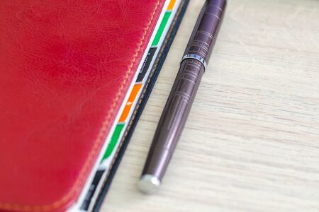 Red notebook with multi-colored roots, labels and metal pen on a wooden background