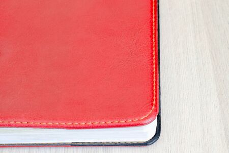 Part of a red diary with a cover under the skin with a stitched edge. Wood surface