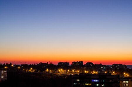 Sunset over the city with silhouettes of houses. Lights of houses and street lamps. Sky blue to red gradient
