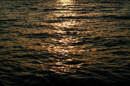 Bright reflection of sunlight on the waves in dark water. Sea at sunset. Evening on the beach Фото со стока