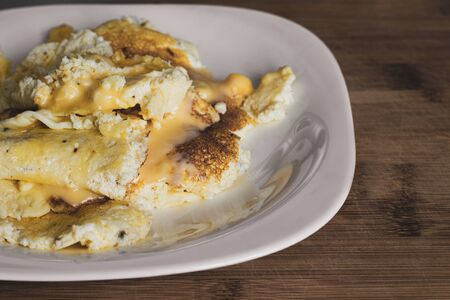 Juicy yellow omelet with melted cheese on a white plate. Fried crust. The surface of the dark wood. Healthy eating concept. Close-up