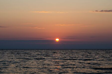 The bright red sun sets over the sea horizon. The sun in the horizontal clouds. The concept of a calm end to a hard day