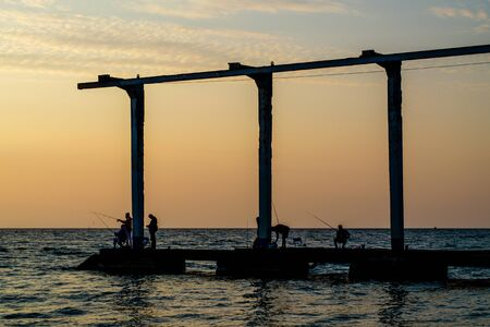 Sochi, Russia - October 19, 2019: Dark silhouettes of fish with fishing rods on a breakwater. A berth for lifting yachts to the shore. Men on vacation. Sea at sunset. The sky is warm Фото со стока