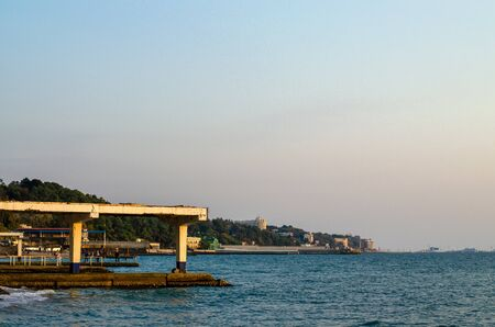 Sea coast with infrastructure: pier, breakwaters, moorings, buildings and green vegetation. Evening at sunset. Copy space