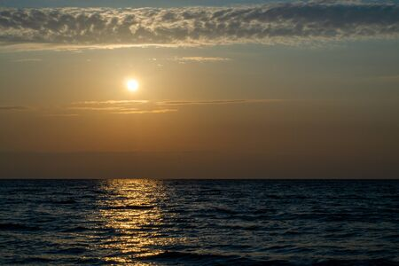 Bright yellow sun over the sea at dusk. Horizontal strip of clouds. The path of sunlight on the waves. Copy space Фото со стока