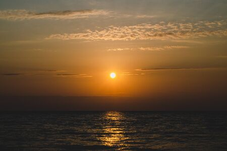 The bright orange sun in the sky. Sunset over the sea water. Sunlight behind the clouds. Light path on the waves. . Copy space