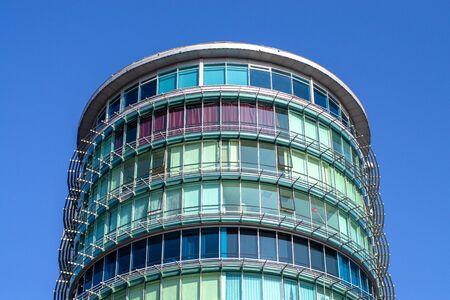 Alexandria shopping center. Semicircular tall modern building. Gss and steel facade. Blue sky. Фото со стока