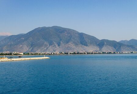 High mountain with greenery by the Mediterranean Sea. The town at the foot of the mountain. Breakwater Фото со стока