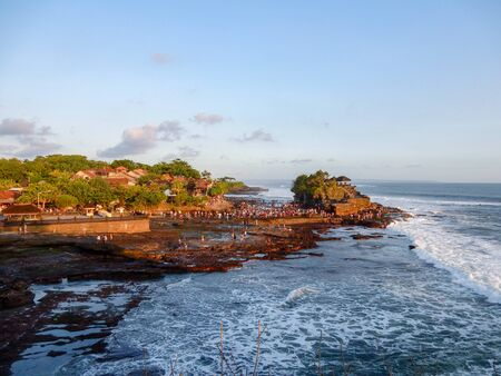 Pura Tanah Lot, Bali, Indonesia - May 25, 2016: crowd of tourists at sunset visiting a temple on the island at low tide Фото со стока