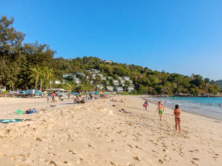 Kata Noi Beach, Phuket, Taliand - May 10, 2016: sandy beach with people stretching into the distance. Bungalow on the hill. Turquoise sea and blue sky